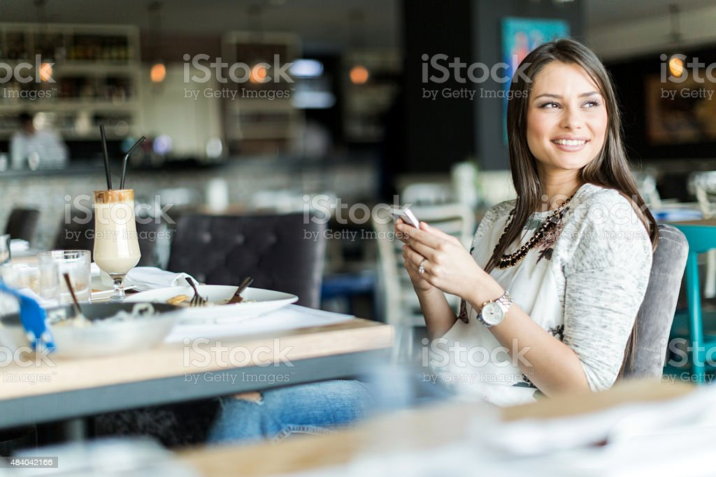 Beautiful lady sitting in a bar and holding a phone stock photo