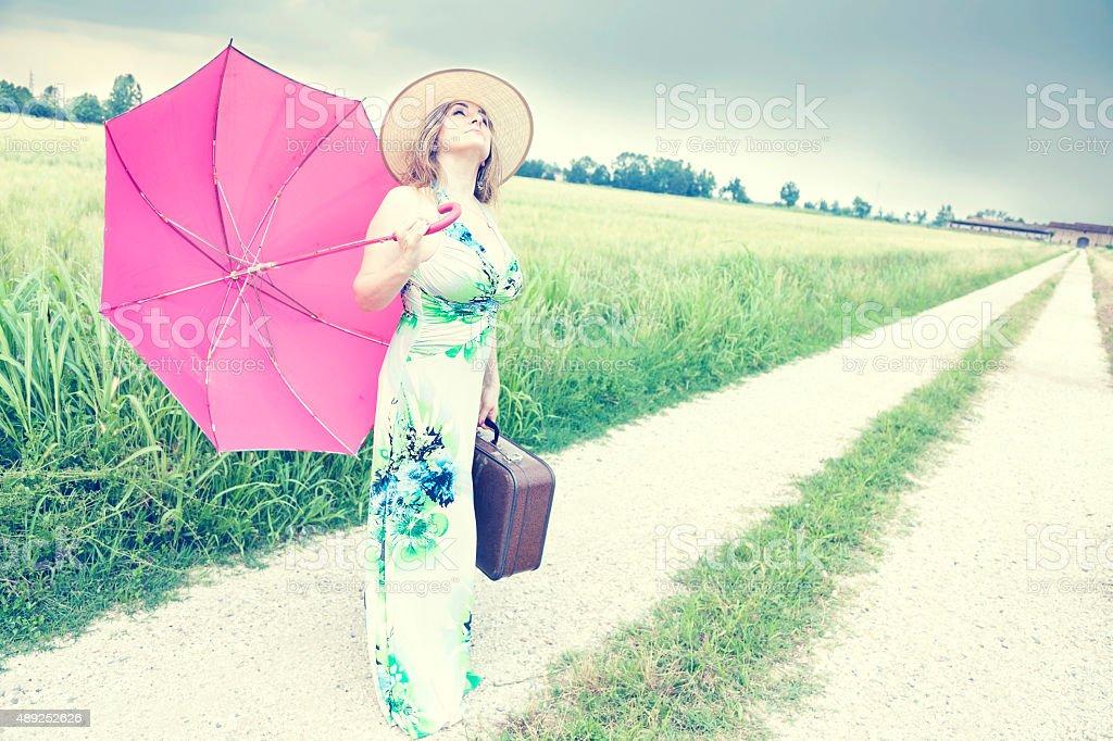 beautiful lady walking on a path in the rain stock photo