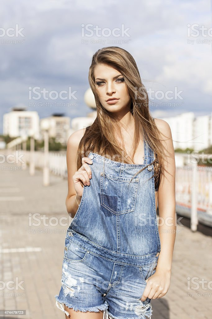 beautiful lady with long silky hair in denim short overalls stock photo