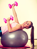 Beautiful lady with pink dumbbells.