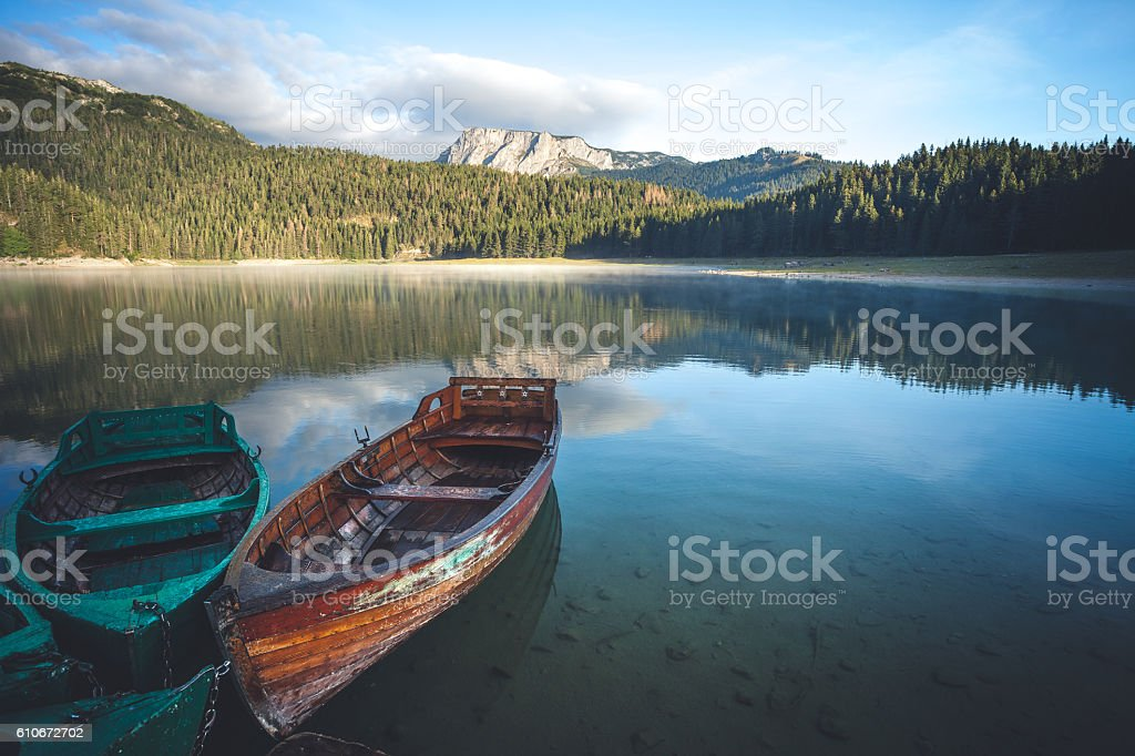 Beautiful lake and old boats in the mountains stock photo