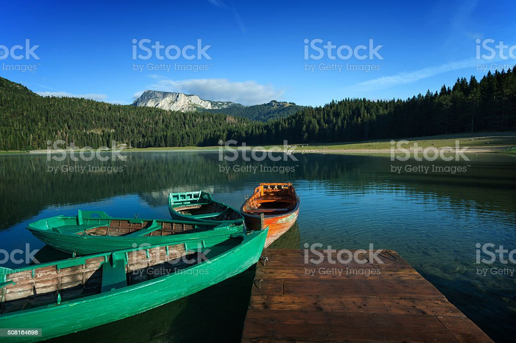 Beautiful lake in mountains and wooden boats at the pier stock photo