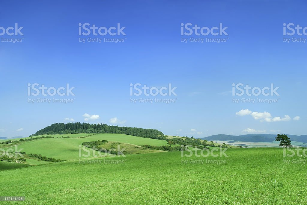 Beautiful landscape of green hills under a blue sky royalty-free stock photo