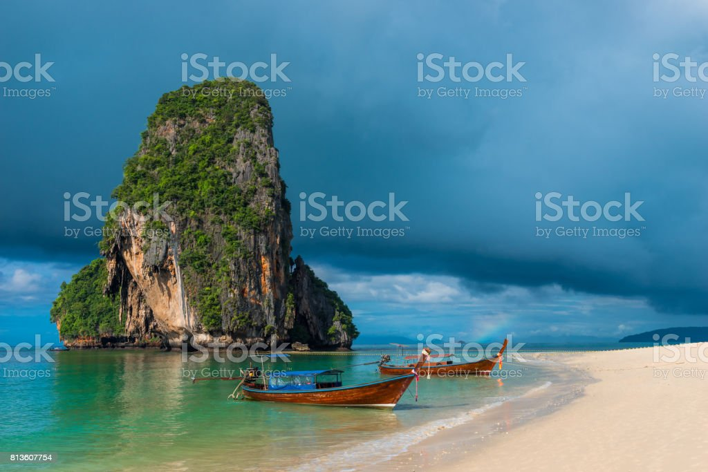 A beautiful landscape of heavy rain clouds and Thai boats near the sandy beach of Phra Nang stock photo