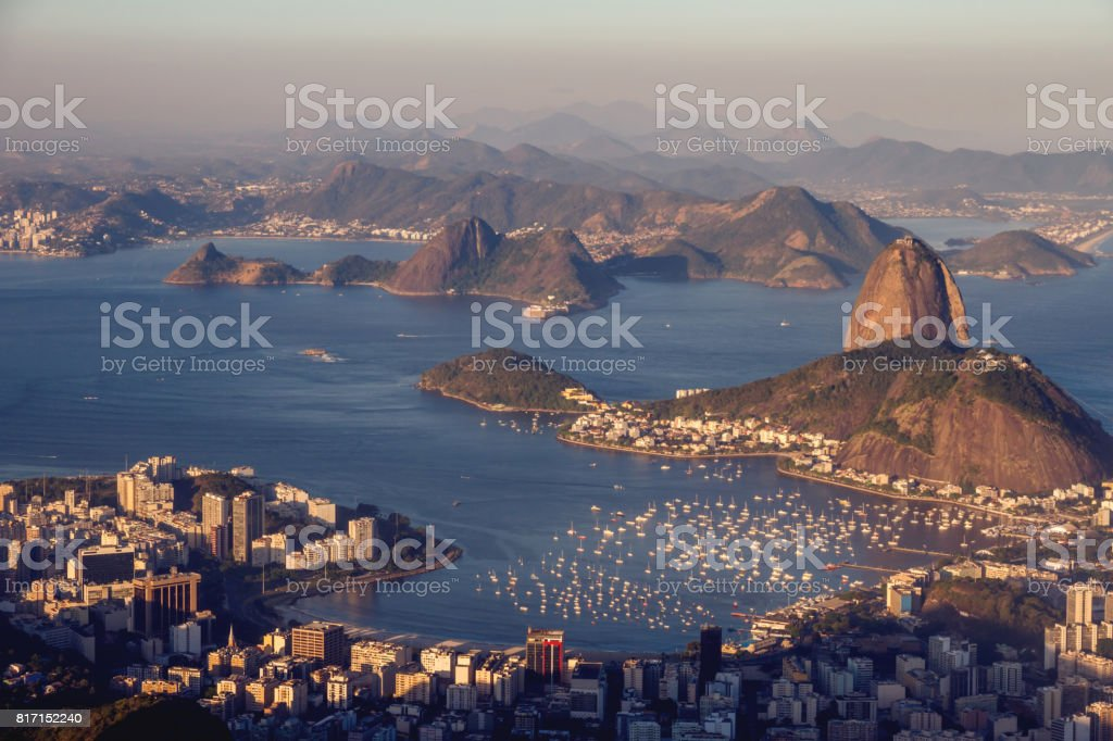Beautiful landscape of the Sugarloaf mountain in the sunset. Yachts nearby, Guanabara bay, Urca and Botafogo districts. Rio de Janeiro, Brazil. stock photo