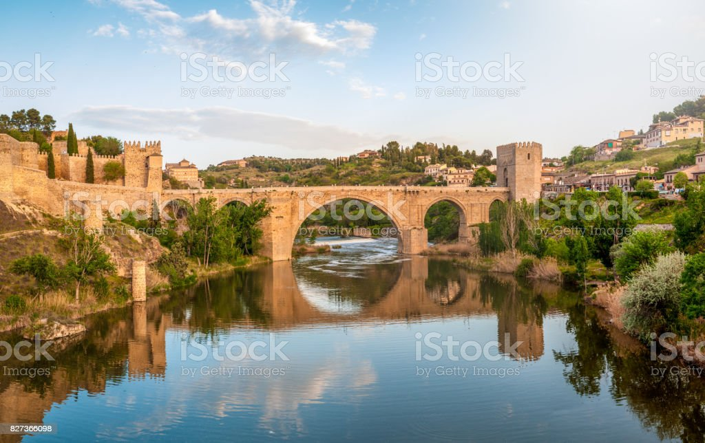 Beautiful landscape of Toledo in Spain. Stone bridge across calm river. Blue sky reflected in crystal clear water. Big fort and country houses in background. Popular tourist place in Europe. stock photo