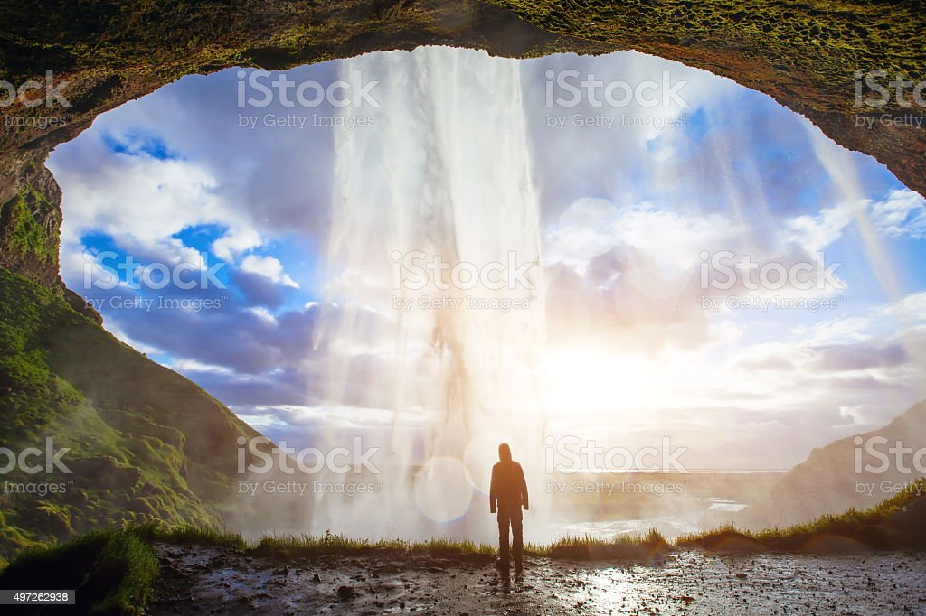 beautiful landscape, person looking at incredible waterfall in Iceland stock photo