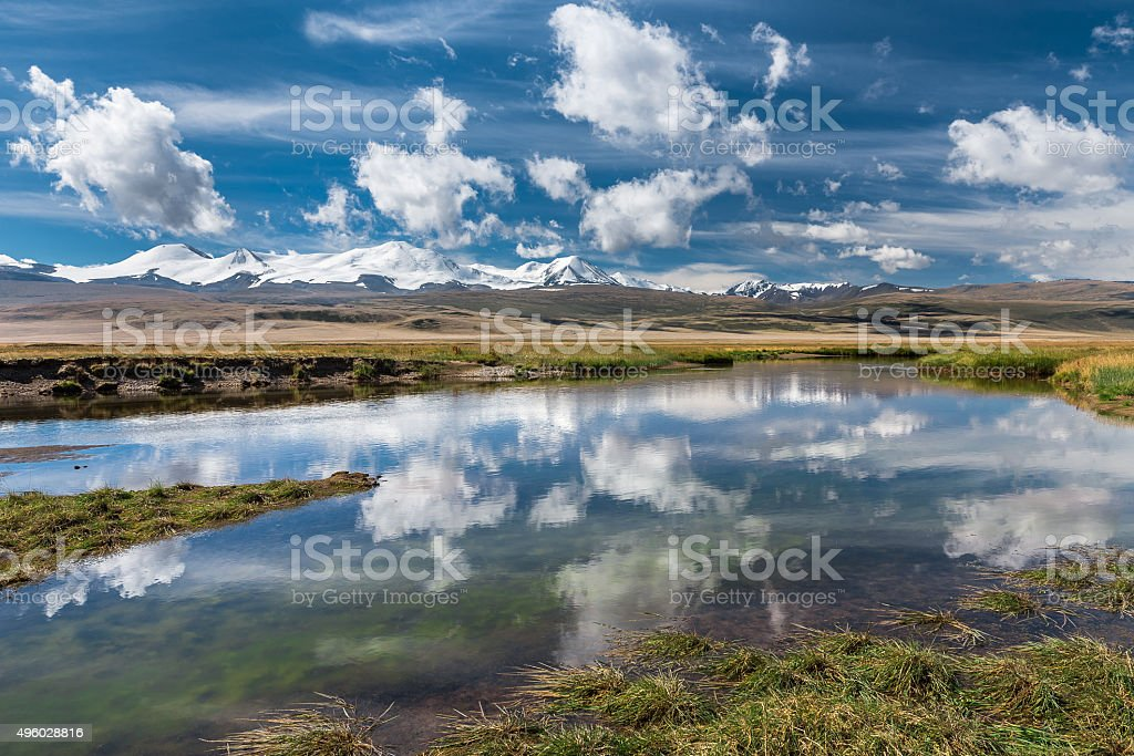 Beautiful landscape with snowy mountains, river  and blue sky stock photo