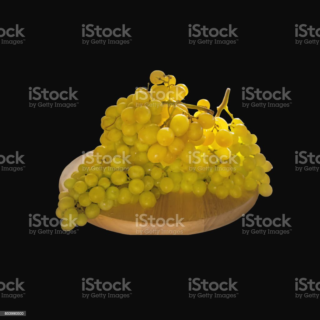 Beautiful large bunch of white grapes lying on a round Board. Isolated on a black background stock photo