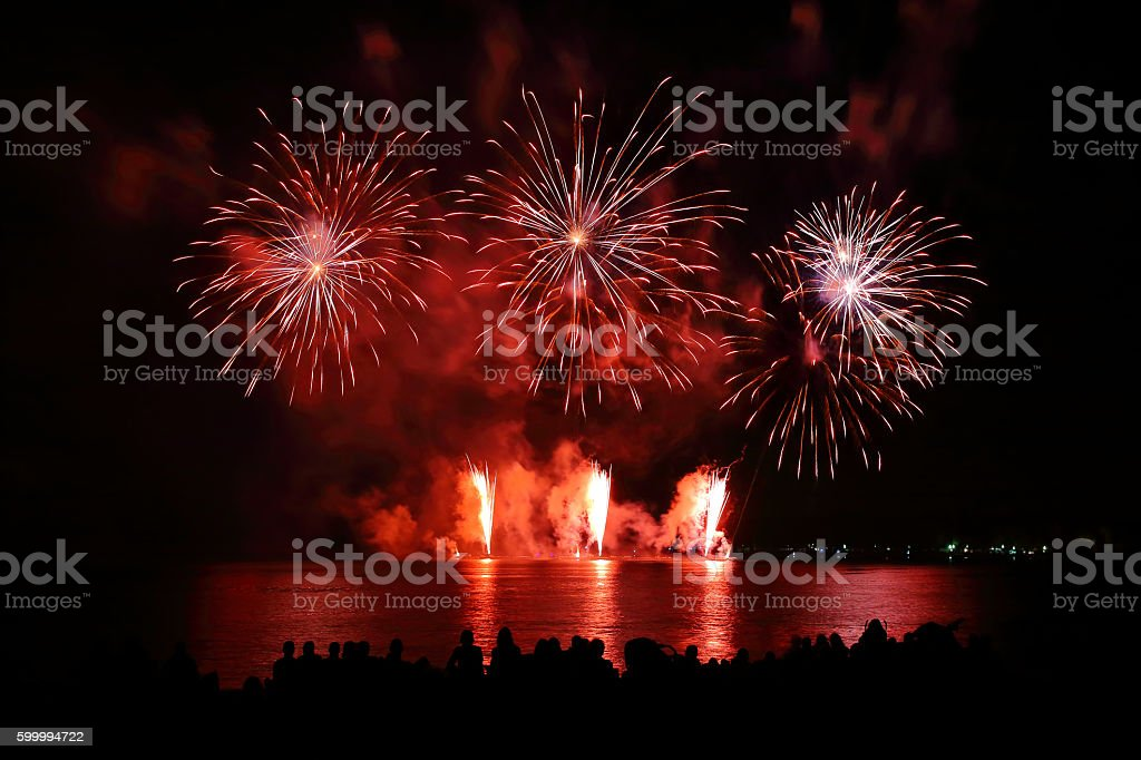 Beautiful large red fireworks display with unrecognizable crowd people watching stock photo