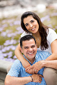 Beautiful latin couple embracing and smiling at camera