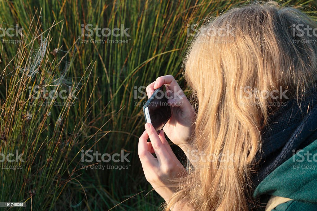 Taking photo with mobile phone Latvian outdoor girl stock photo