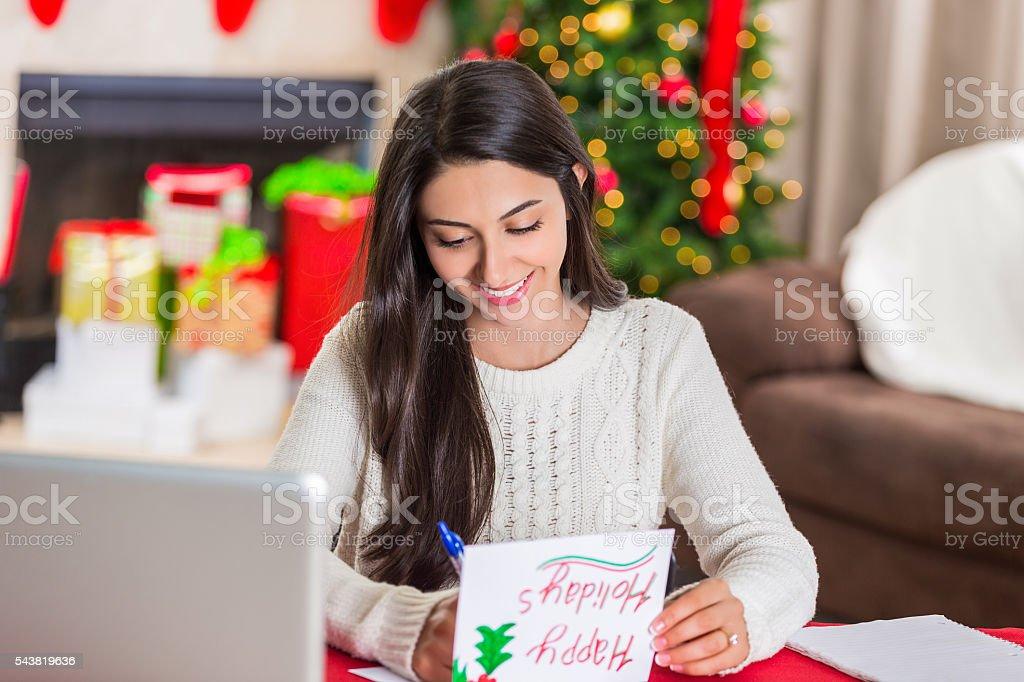 Beautiful Lebanese woman writes in Christmas card stock photo