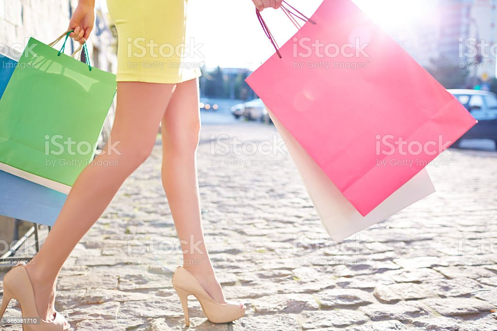 Beautiful legs of woman carrying multi-colored shopping bags stock photo