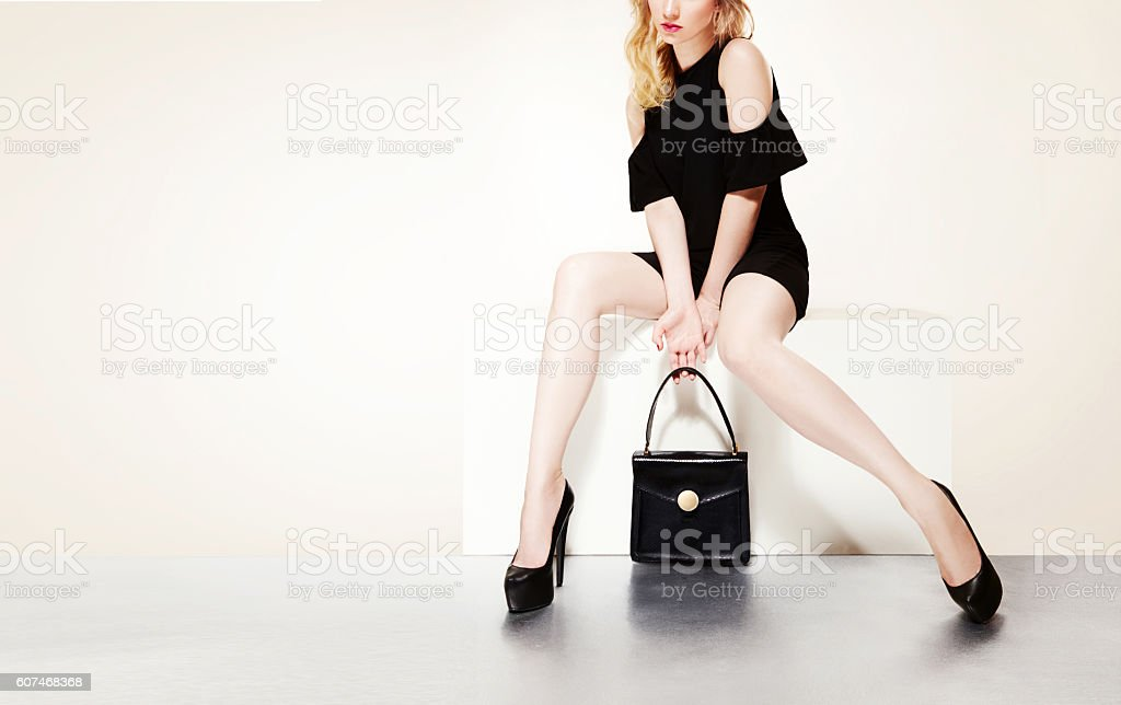 Beautiful legs with black heels and handbag purse woman sitting. stock photo