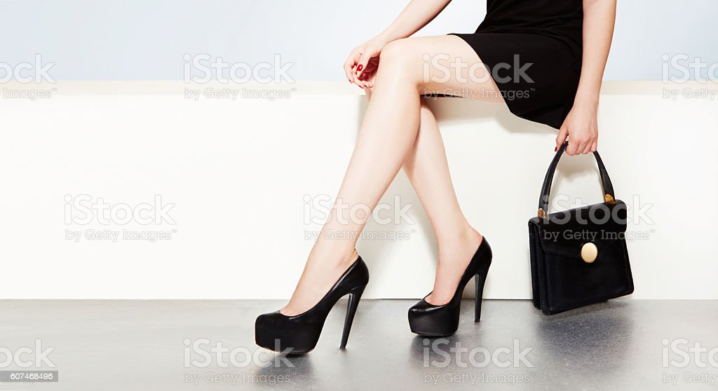 Beautiful legs with black heels and handbag purse woman witting. stock photo