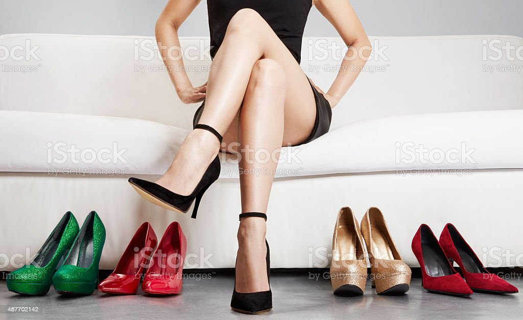 Beautiful legs. Woman with many shoes. choosing.Body care. stock photo