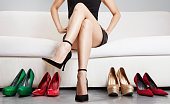 Beautiful legs. Woman with many shoes. choosing.Body care.