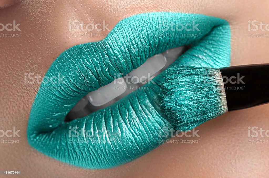 Beautiful lips with a brush. stock photo