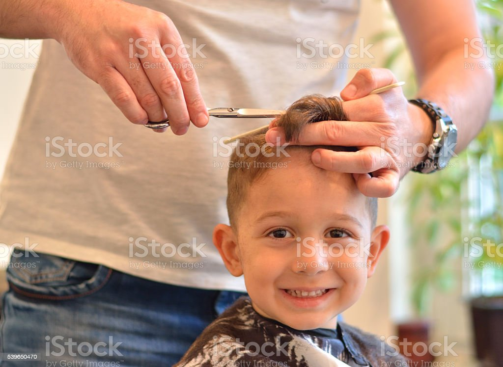 Beautiful Litlle Boy Getting a Haircut stock photo