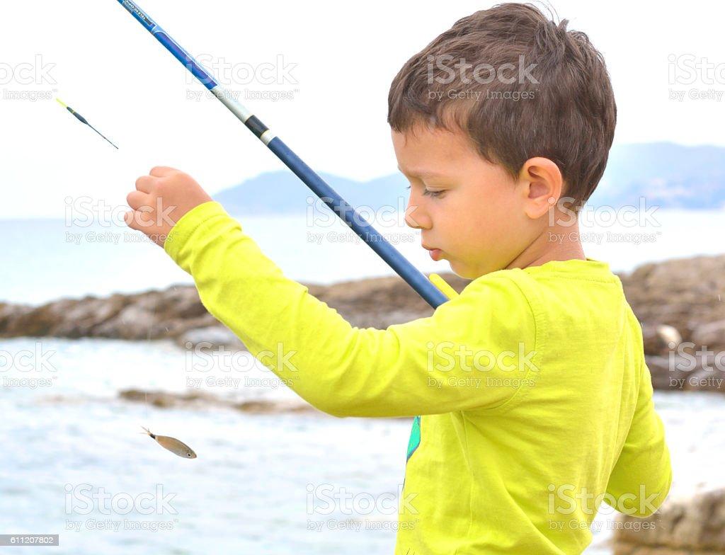 Beautiful Little Boy Catching a Fish stock photo