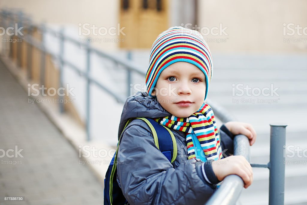 Beautiful little boy in bright striped hat and scarf stock photo