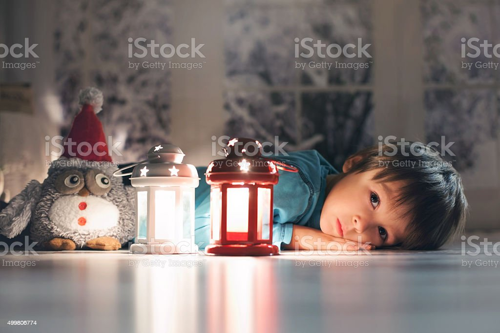 Beautiful little boy, lying down on floor, looking at candle stock photo