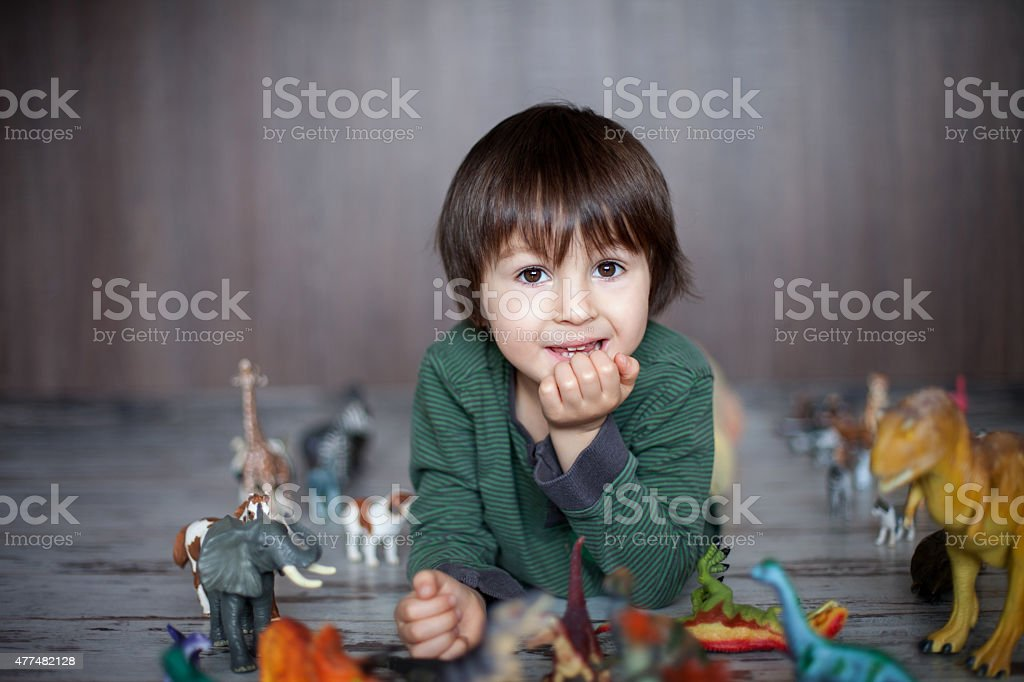 Beautiful little boy, smiling at camera, animals and dinosaurs a stock photo