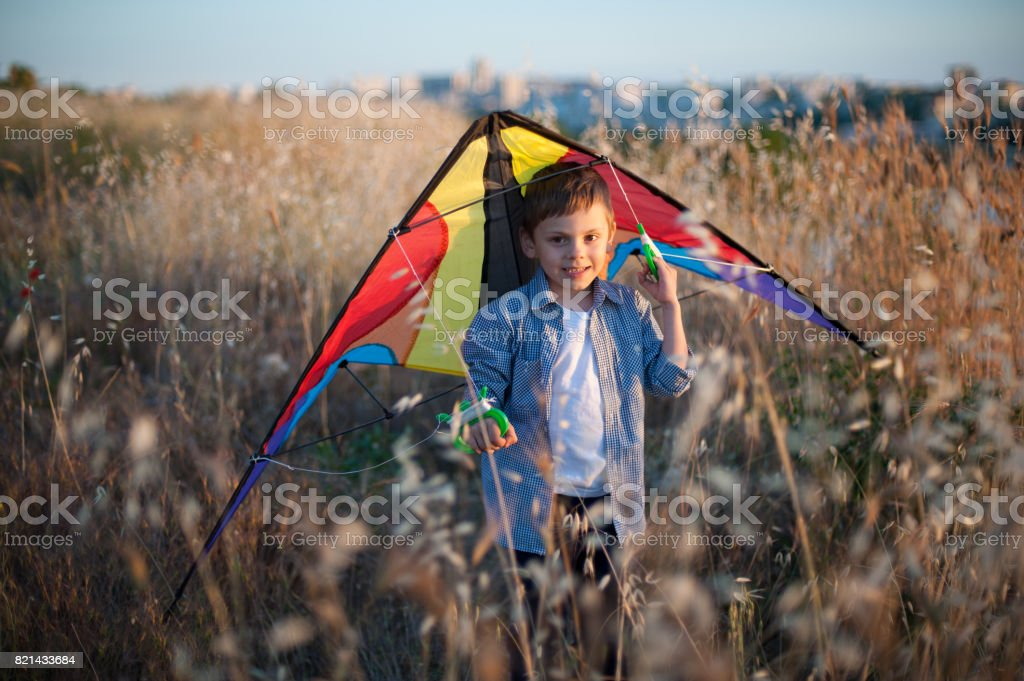Beautiful little boy with a kite behind his back stock photo