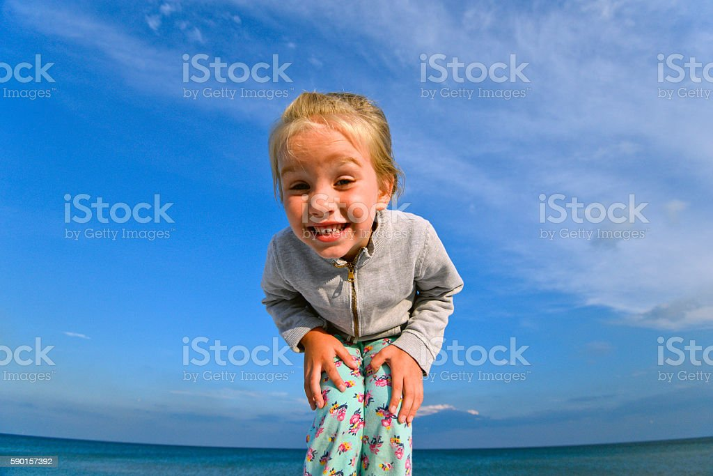 Beautiful little cute girl smiling happily at you stock photo