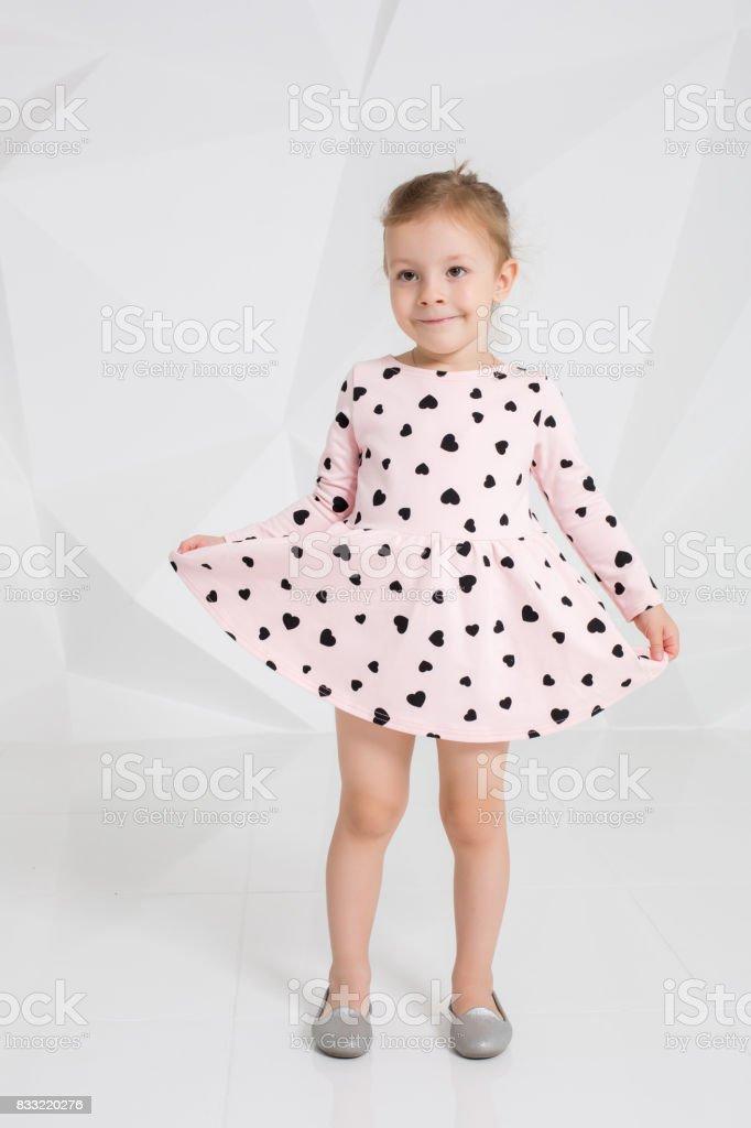 Beautiful little fashion model on white studio background. Portrait...