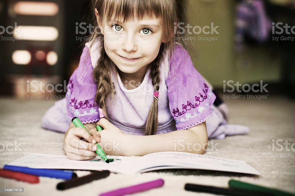 Beautiful little girl and her coloring book. royalty-free stock photo