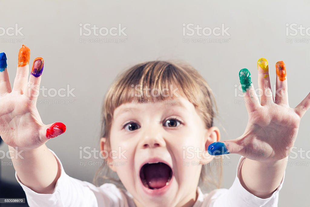 beautiful little girl draws a finger paints, children's palms stock photo