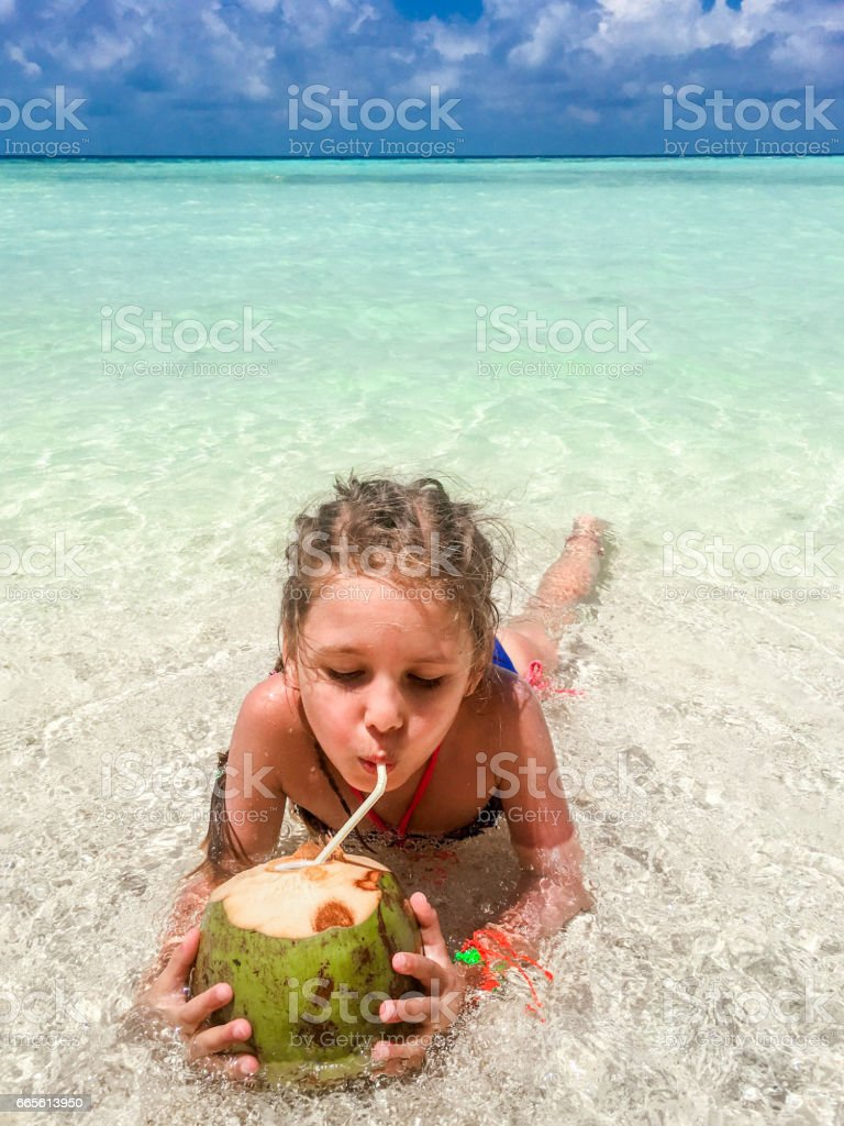 Beautiful Little Girl Drinking Coconut On The Beach stock photo