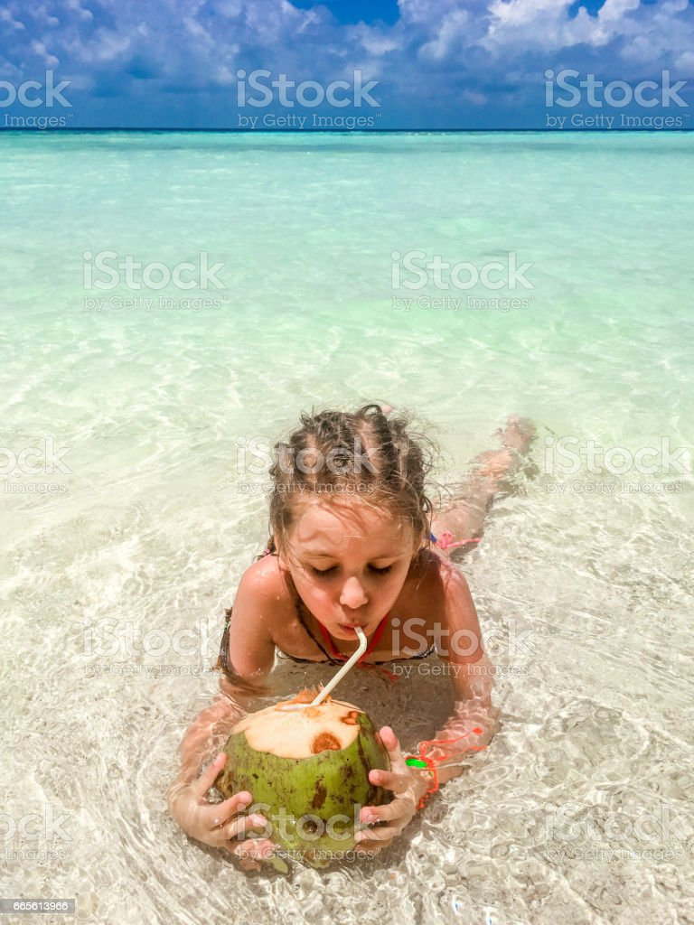 Beautiful Little Girl Drinking Coconut On The Beach stock photo