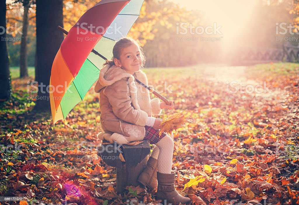 Beautiful little girl having fun at sunset in autumn forest stock photo