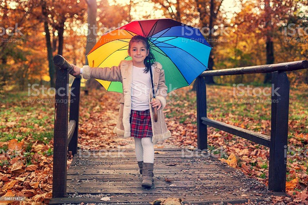 Beautiful little girl having fun in autumn forest stock photo