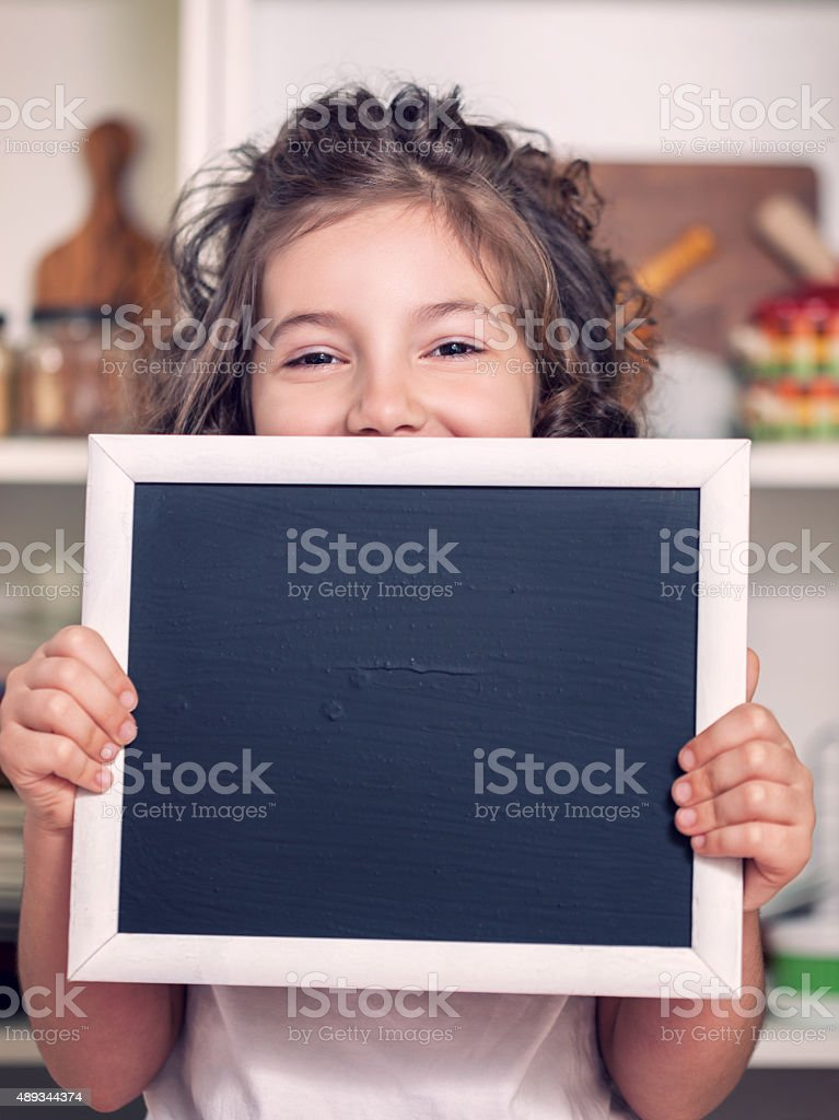 Beautiful Little Girl Holding Blank Blackboard stock photo