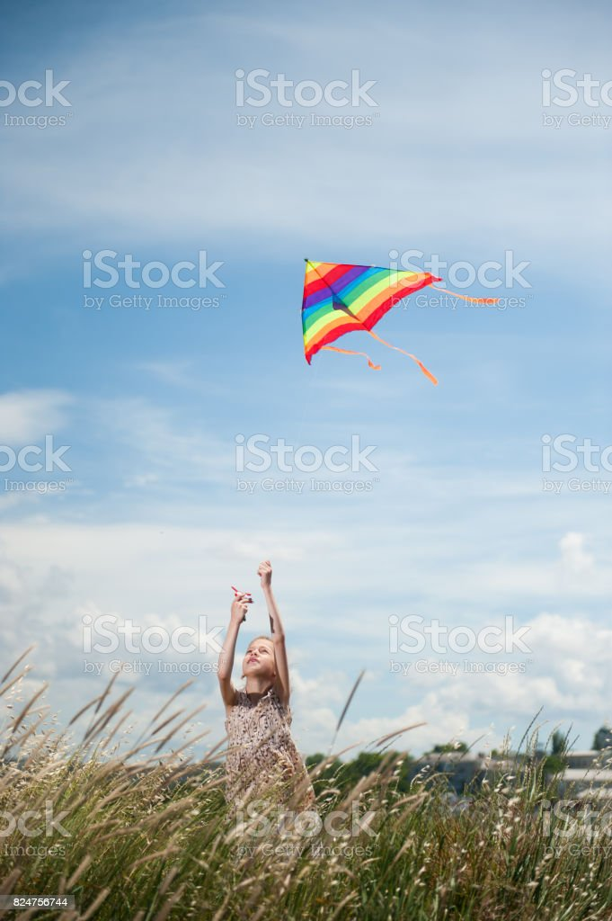 beautiful little girl holding flying kite in the field on summer sunny day stock photo