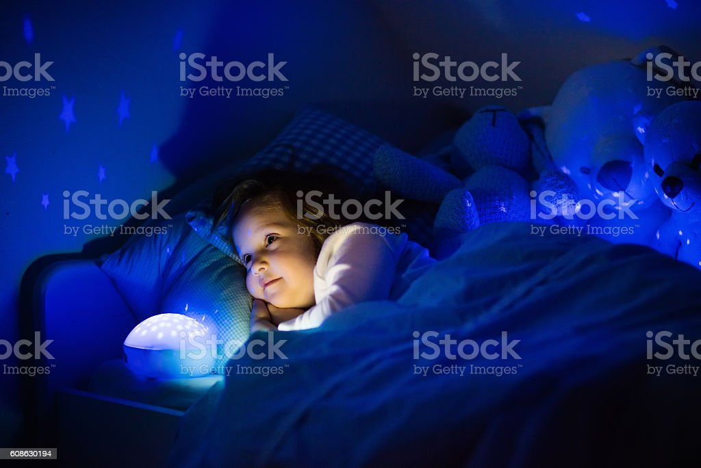 Beautiful little girl in bed with night lamp stock photo