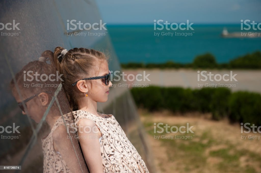 beautiful little girl in fashionable dress and sunglasses stock photo