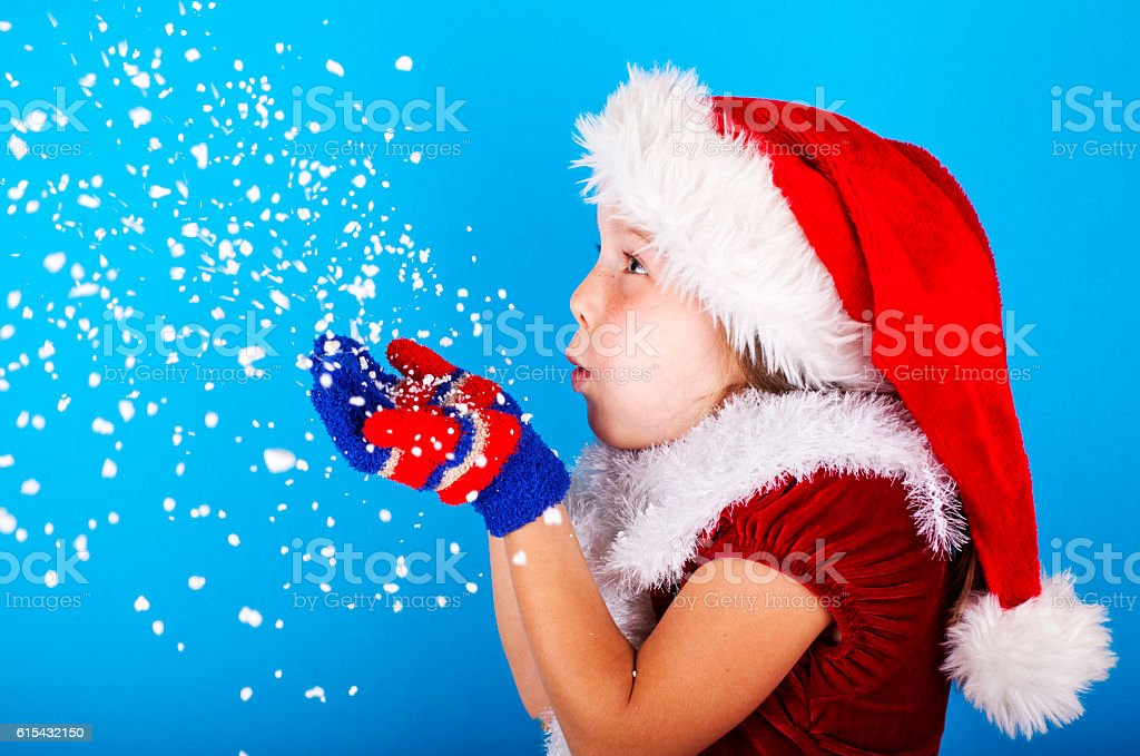Beautiful little girl in Santa Claus hat blowing snowflakes stock photo