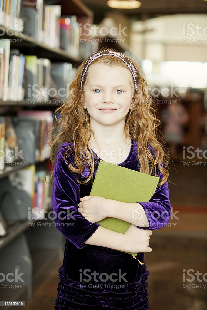 Beautiful little girl in the library holding a book royalty-free stock photo