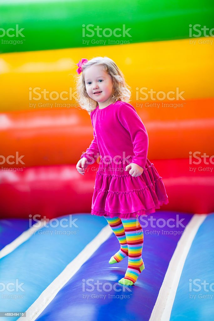 Beautiful little girl jumping and bouncing stock photo