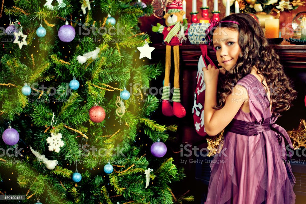 Beautiful little girl looking for Christmas gifts stock photo