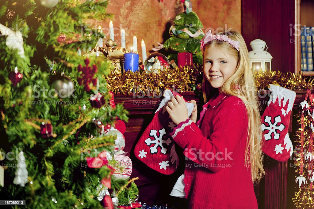 Beautiful little girl looking for Christmas gifts royalty-free stock photo
