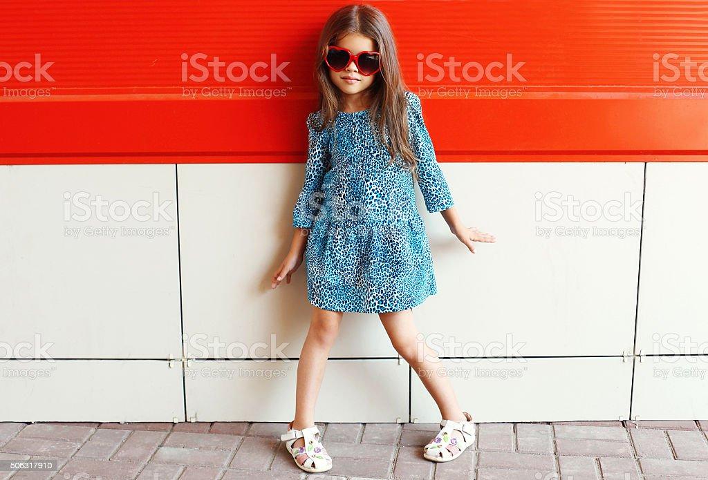Beautiful little girl model wearing a leopard dress and sunglass stock photo