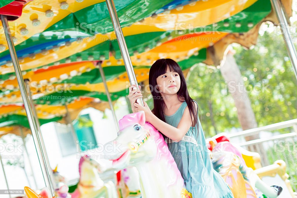beautiful little girl on a retro carousel ride stock photo