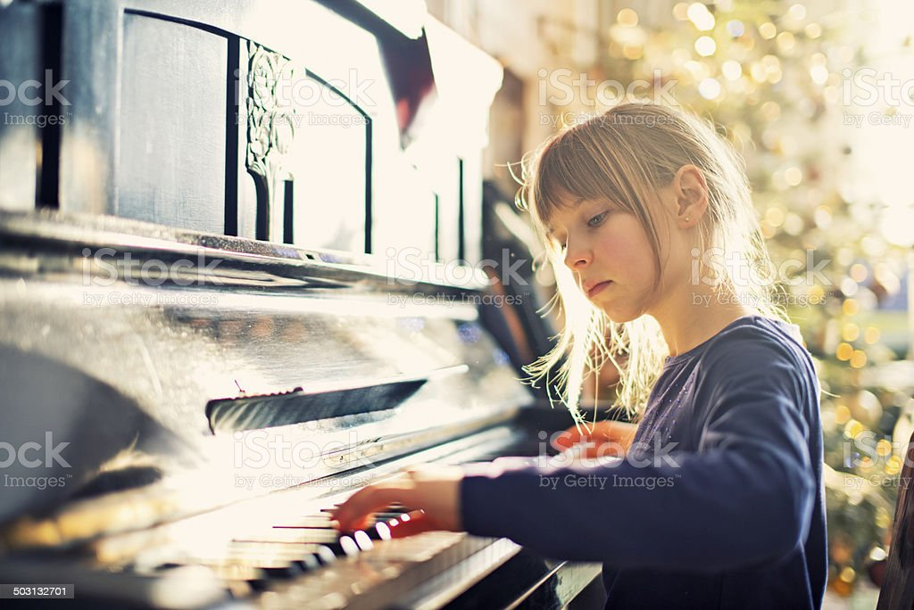 Beautiful little girl playing on grandmother piano stock photo