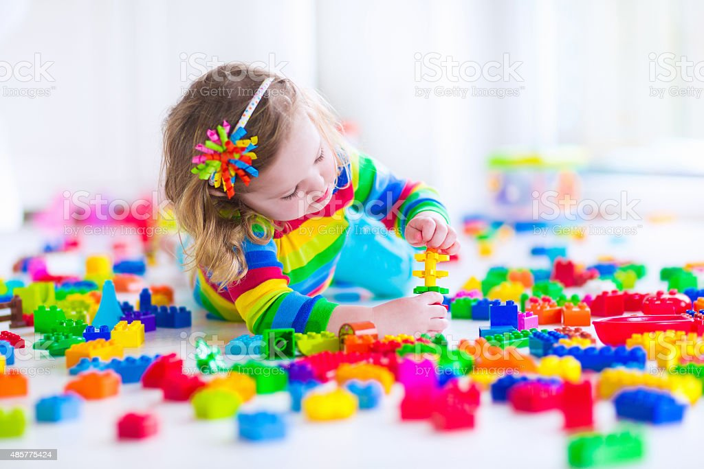 Beautiful little girl playing with colorful toy blocks stock photo